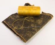 Rouleau coloré de fil sur un morceau de cuir avec une aiguille Image stock