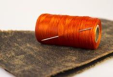 Rouleau coloré de fil sur un morceau de cuir avec une aiguille Photos libres de droits