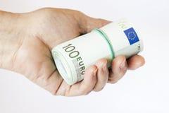 Rouleau de billets de banque dans la main Photographie stock