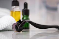 Rouleau de Derma, serviette, pétrole cosmétique jaune et bouteilles vertes de compte-gouttes de sérum pour l'anti traitement viei image stock