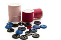 Rouleau de fil de couture rose et rouge avec les boutons bleus et noirs Images libres de droits