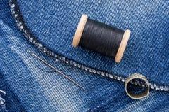 Rouleau de fil et de jeans noirs Photographie stock