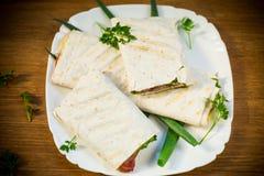 Rouleau de pain pita avec des feuilles, des verts et la saucisse de laitue dans un plat images libres de droits