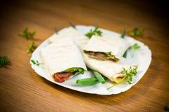 Rouleau de pain pita avec des feuilles, des verts et la saucisse de laitue dans un plat photo stock