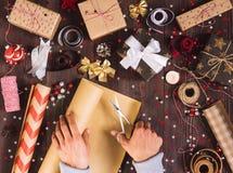 Rouleau de participation de main d'homme de papier d'emballage de papier d'emballage avec des ciseaux pour couper le boîte-cadeau Photographie stock