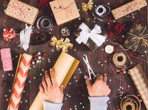 Rouleau de participation de main d'homme de papier d'emballage de papier d'emballage avec des ciseaux pour couper le boîte-cadeau Images stock