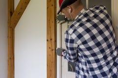 Rouleau de peinture avec des échantillons de peinture Un bricoleur installant une dalle en bois fermante pour photographie stock