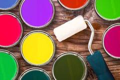 Rouleau de peinture et boîtes en fer blanc de couleur de couleur sur le fond en bois Images libres de droits