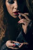 rouleau de poudre d'argent et de drogue, Femme avec des pilules à disposition prenant un Photographie stock libre de droits