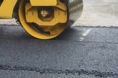 Rouleau de route tout en travaillant pour écraser l'asphalte pour condenser Images libres de droits