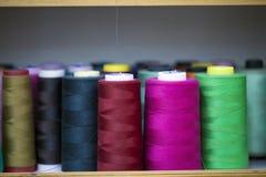 Rouleau de textile de tissu de coton de fibre sur le fil de cordages de bobine et de lumière Photos stock