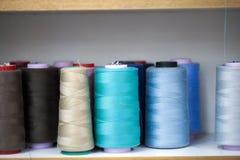 Rouleau de textile de tissu de coton de fibre sur le fil de cordages de bobine et de lumière Images stock
