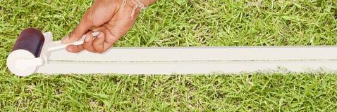 Rouleau et main, peinture blanche Photographie stock