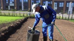 Rouleau professionnel de sol de remplissage de paysagiste avec de l'eau de tuyau Tir statique banque de vidéos