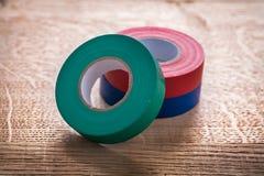 Rouleaux bleus rouges verts de bande d'isolation sur en bois Photographie stock libre de droits