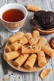 Rouleaux de gaufrette, gâteaux aux pépites de chocolat et une tasse de thé sur une table en bois image libre de droits