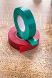 Rouleaux de rouge et de vert de bande d'isolation sur en bois Photographie stock