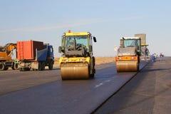 Rouleaux de route nivelant le trottoir frais d'asphalte sur une piste Photographie stock libre de droits