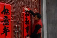 Rouleaux du ` s de nouvelle année de courrier d'homme, couplets de festival de printemps et Mars chinois à la porte rouge en Chin Images libres de droits