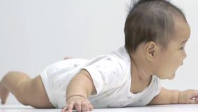 Roulement chinois asiatique mignon de bébé sur son ventre dans le mouvement lent clips vidéos