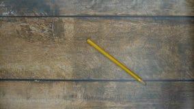 Roulement de crayon sur une table en bois banque de vidéos
