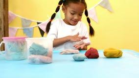 Roulement heureux de fille modelant l'argile dans une boule clips vidéos
