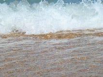 Roulement mousseux de vague sur la plage images stock