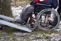 Roulement vers le haut d'un handicapé dans le fauteuil roulant dans une maison de campagne Image libre de droits