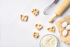 Roulent avec la farine de blé, goupille, battent, les oeufs, coupeurs de biscuit Vue supérieure sur une table blanche avec un esp Images stock