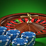 Roulette. Wheel with chips on green background Stock Image