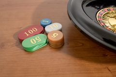 A roulette and colored casino chips on a wood table stock image