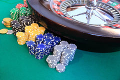 Roulette and gambling chips. Green table, gambling chips and roulette in a casino Royalty Free Stock Photography