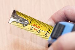 Roulette in the hand. A metal tape measure with divisions in centimeters and feet stock photos