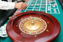 Roulette para jugar el póker en el fondo de la tabla con los jugadores imagen de archivo