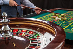 Roulette and piles of gambling chips on a green table. Royalty Free Stock Photos