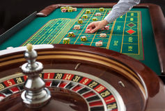 Roulette and piles of gambling chips on a green table. Royalty Free Stock Images