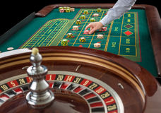 Roulette and piles of gambling chips on a green table. Stock Photos