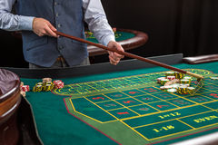 Roulette and piles of gambling chips on a green table. Royalty Free Stock Photography