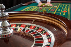 Roulette and piles of gambling chips on a green table. Stock Photography