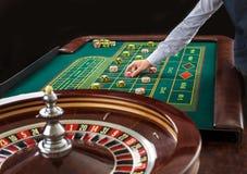 Roulette und Stapel des Spielens bricht auf einer grünen Tabelle ab Stockbilder