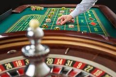 Roulette und Stapel des Spielens bricht auf einer grünen Tabelle ab Lizenzfreies Stockbild