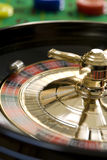 Roulette wheel. Spinning roulette wheel with ball and gambling chips stock photography