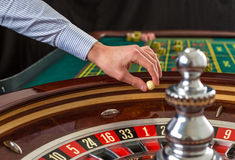 Roulette wheel and croupier hand with white ball in casino. Close up details royalty free stock images