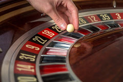 Roulette wheel and croupier hand with white ball in casino Stock Photo