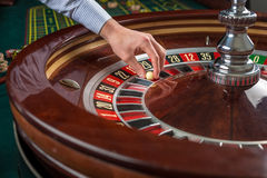 Roulette wheel and croupier hand with white ball in casino Royalty Free Stock Photo