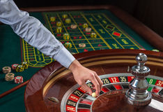 Roulette wheel and croupier hand with white ball in casino Royalty Free Stock Photography