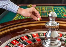 Roulette wheel and croupier hand with white ball in casino Stock Image