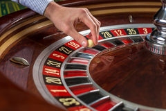 Roulette wheel and croupier hand with white ball in casino Royalty Free Stock Images
