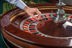 Roulette wheel and croupier hand with white ball in casino Royalty Free Stock Photos