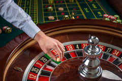 Roulette wheel and croupier hand with white ball in casino Stock Photos
